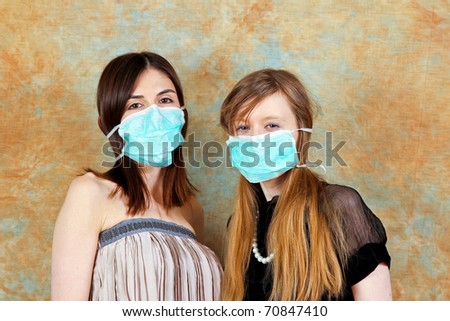 Two young women with protective medical masks - stock photo