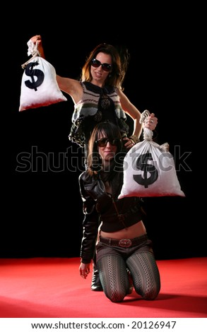 Two young women with sack bags full of money. Focus on money sack - stock photo