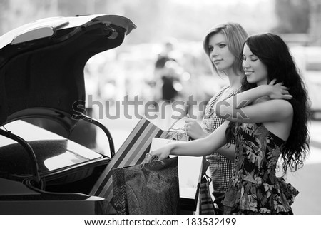 Two young women with shopping bags at the car trunk - stock photo