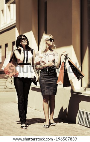 Two young women with shopping bags at the mall windows - stock photo