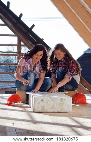 Two young women workers sitting on under construction roof, and control building in accordance with drawing - stock photo
