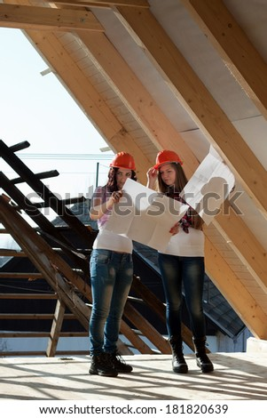 Two young women workers standing on under construction roof, and control building in accordance with drawing - stock photo