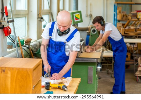 two young worker in blue dungarees in a carpenter's workshop - stock photo