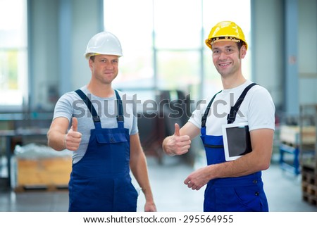 two young worker in factory with thumb up - stock photo