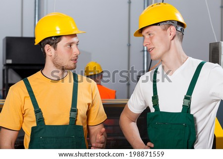Two young workers in production area talking and looking at each other - stock photo
