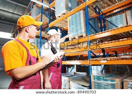 two young workers man in uniform in front of warehouse rack arrangement stillages - stock photo