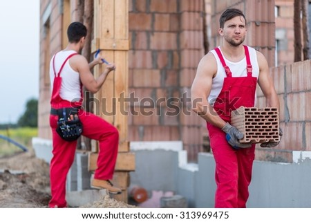 Two young workmen employed at construction site - stock photo