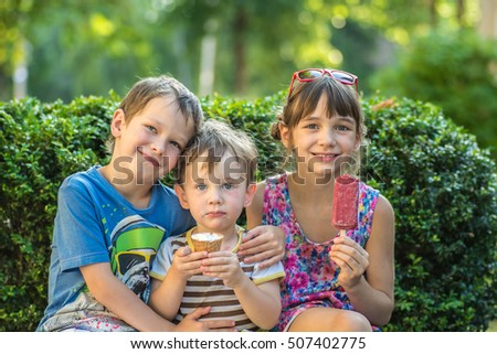 Two younger brother and sister eating an ice cream in summer