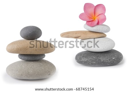 Two zen , stone stacks, one with a pink frangipani or plumeria flower