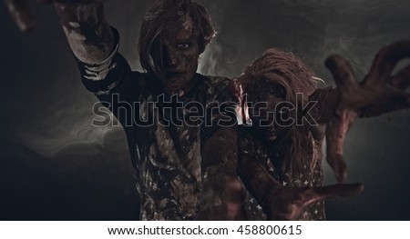Two zombies standing in smoke on black background. Apocalypse.