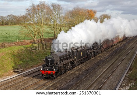 TWYFORD, UK - DECEMBER 11: A pair of vintage ex LMS Black 5 steam locos take the Cathedrals Express passenger charter train toward Bristol on December 11, 2014 in Twyford - stock photo