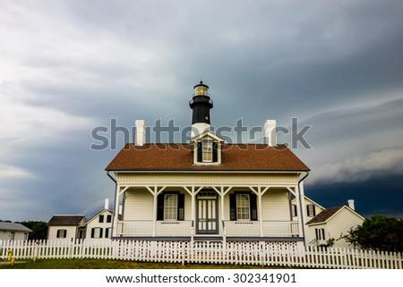 tybee island beach lighthouse with thunder and lightning - stock photo