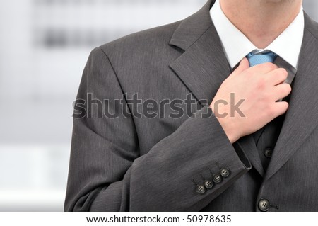Tying a tie. Businessman in gray suite tying blue tie. - stock photo