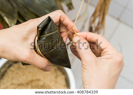 Tying a wrapped dumpling in banana leaf. - stock photo