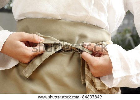 Tying  an apron around the waist - stock photo
