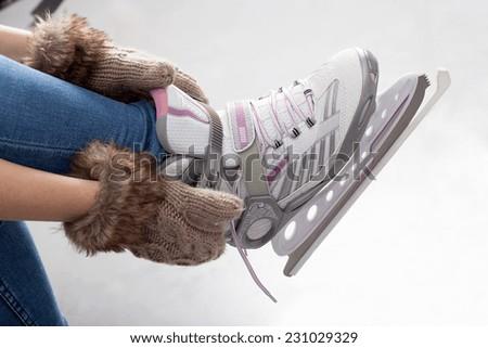 Tying laces of ice figure skates, horizontal - stock photo
