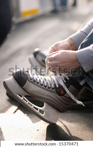Tying laces of ice hockey skates at skating rink