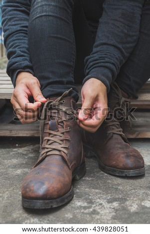 Tying Shoes on wooden floor, Men fashion brown leather boots. - stock photo
