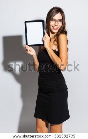 tylish girl in a black business dress and sunglasses standing on a white background with a snow-white smile, smiling, picture with depth of field, selective focus on the tablet, instagram filter - stock photo