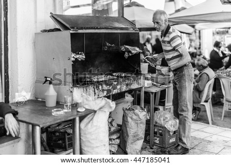 TYMBAKI, CRETE - APRIL 22. Man put Souvlaki on a charcoal barbecue in the village Tymbaki in southern Crete on April 22, 2016. Saturday is Farmers market in the village. All folks comes to the market - stock photo