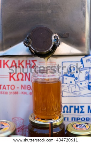 TYMBAKI, CRETE,GREECE - APRIL 22. Honey bottling on the farmers market in the village Tymbaki in south-central of Crete on April 22, 2016. Thyme honey is a speciality from the mountain region on Crete - stock photo