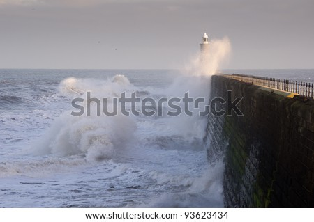Tynemouth north pier and waves / Waves crashing against Tynemouths pier and lighthouse - stock photo