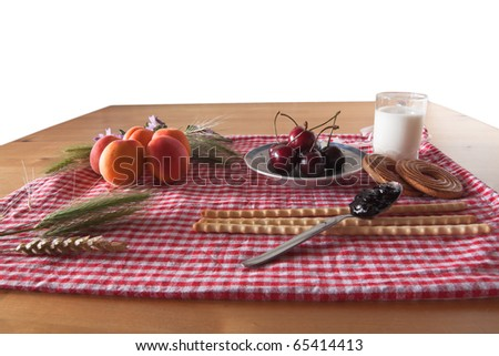 Type of food for a summer break. There are apricots, cherries, milk, jam, biscuit and bread on a checked tablecoat with some flowers and wheat. White background isolated.
