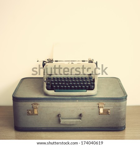 Typewriter and vintage suitcase  - stock photo