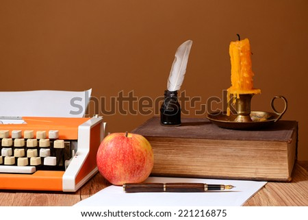 Typewriter, books and apple on the wooden table - stock photo