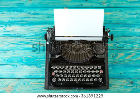 Typewriter on a bright blue wooden table. Time for the colorful history of creation. Top view desk - stock photo