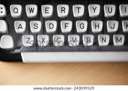 Typewriter qwerty keys on wooden desk - stock photo