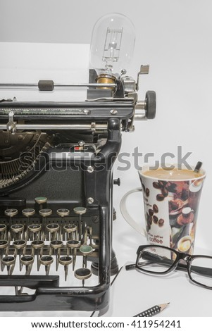 typewriter with blank book, reading glasses and an old light bulb - stock photo