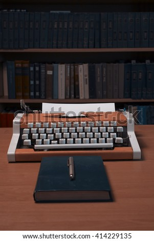 Typewriter with blank sheet of paper with many books in background - stock photo