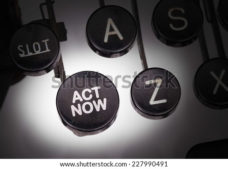 Typewriter with special buttons, act now - stock photo