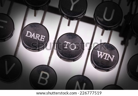 Typewriter with special buttons, dare to win - stock photo