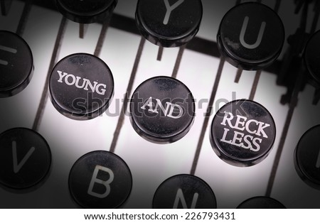 Typewriter with special buttons, young and reckless - stock photo