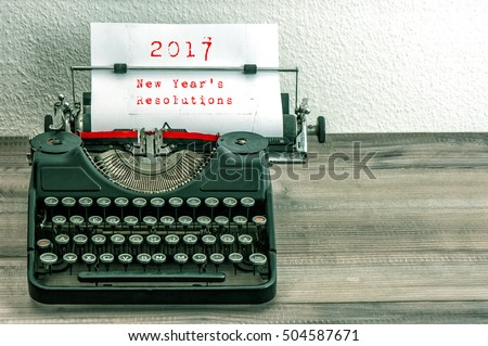 Typewriter with white paper page on wooden table. sample text 2017 New Year's Resolutions