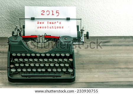Typewriter with white paper page on wooden table. sample text 2015 New Year's Resolutions. vintage style toned picture - stock photo