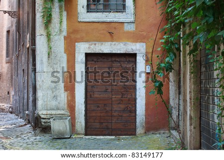 Typical alley in Rome, with orange color surrounding the entrance door