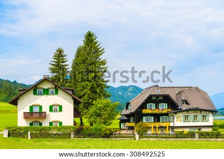 Typical alpine houses on green meadow in summer season, Weissensee lake, Austria - stock photo