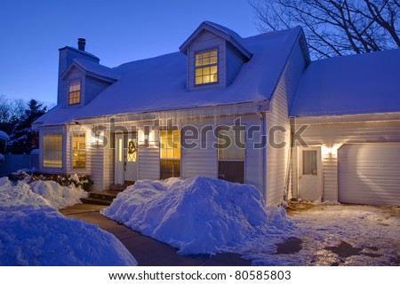 Typical American home with icy winter snow - evening twilight - cape cod style - stock photo