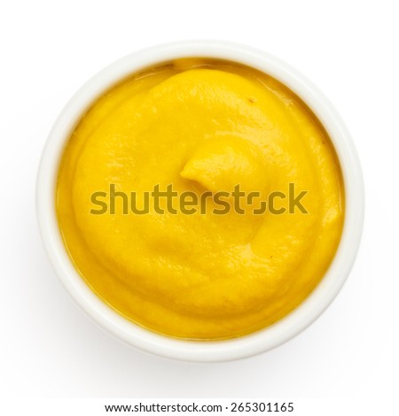 Typical american smooth yellow mustard in round dish from above on white.