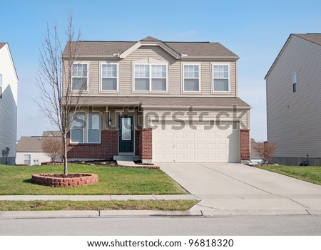 Typical American two story residential home made of brick and vinyl siding in a suburban neighborhood in winter. - stock photo