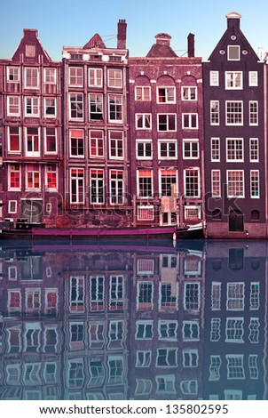 Typical Amsterdam houses reflected in the canal with blue sky background