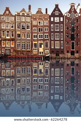 typical amsterdam houses reflected in the canal with blue sky background - stock photo