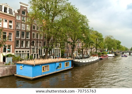 Typical Amsterdam's canal with blue house boat and boats in summer sunny day - stock photo