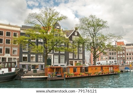 Typical Amsterdam's canal with house boat, Netherlands - stock photo