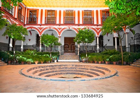 Typical andalusian courtyard with fountain In Seville, Spain. - stock photo