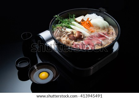 Typical Asian ingridients: marble noodles, bacon, tofu, mushrooms, onion and greens preparing in a cooker. Asian food. - stock photo