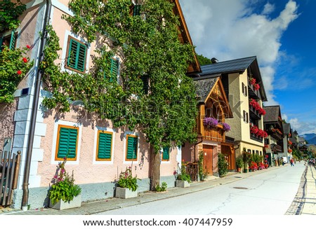 Typical austrian alpine house with colorful flowers on balcony and pear tree,Hallstatt,Austria,Europe - stock photo